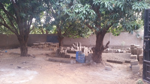 """Image 1 - View from the gate entry looking west. Cement bricks being made in the """"open space"""" of the mango grove."""